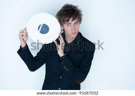 Trendy young man with silver LP record next to head, light studio background and copy space.