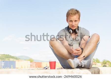 Trendy young millennial man with smart phone, headphones and takeaway coffee sitting outdoors on sunny summer day. Closeup of blonde modern millennial guy. Horizontal, mild retouch, copy space. - stock photo
