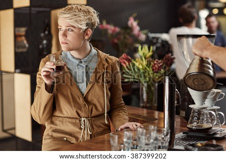 Trendy young woman daydreaming in a cafe with coffee - stock photo