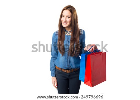 Trendy young woman holding red and blue shopping bags. Over white background - stock photo