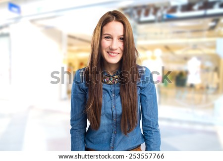 Trendy young woman looking funny. Over shopping center background - stock photo