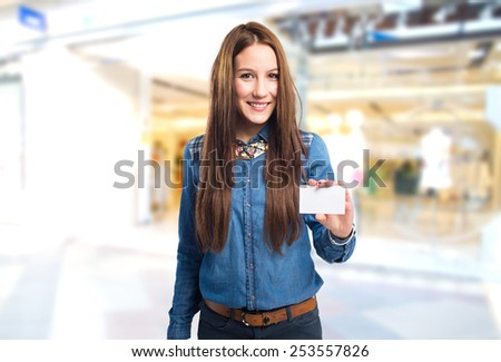 Trendy young woman smiling and holding a white card. Over shopping center background - stock photo