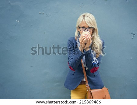 Trendy young woman standing at the wall outdoors and drinking coffee. - stock photo