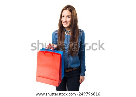 Trendy young woman with different colors shopping bags. Over white background - stock photo