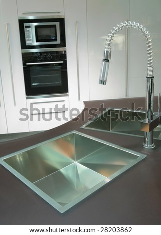 trendys metallic sink with graceful faucet on the super-modern kitchen - stock photo