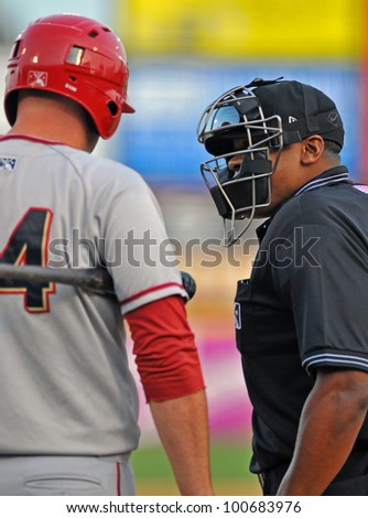 TRENTON, NJ - APRIL 21: Home plate umpire Doug Vines (r) talks to a batter about a strike call during the Eastern League baseball game April 21, 2012 in Trenton, NJ. - stock photo