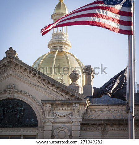 TRENTON, NJ - APRIL 4, 2015: The American Flag waves in front of the gold dome rotunda of the New Jersey State House located in Trenton. The capitol building for the state NJ is located on State St. - stock photo