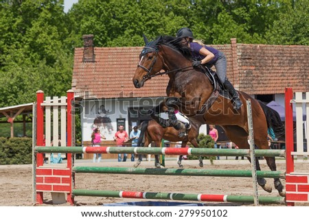 "TRESTINA, CZECH REPUBLIC - MAY 16: Closeup of young blonde horsewoman jumping over the obstacles at ""Equestrian Hobby Series 2015"" on May 16, 2015  in Trestina, Czech Republic."
