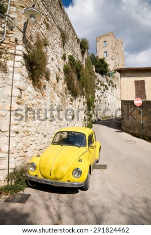 Trevi, Italy - 2014, October 5 : An old yellow Volkswagen beetle standing in the medieval streets of the town of Trevi in Umbria, Italy - stock photo