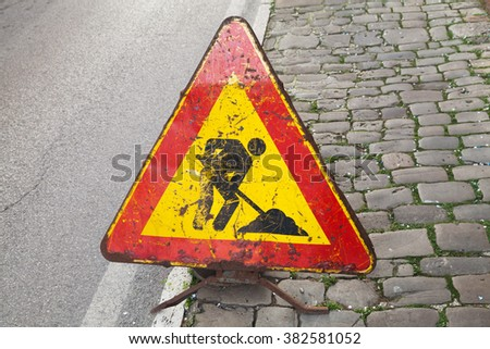 Triangle red and yellow roadsign on urban roadside. Men at work, road under construction - stock photo