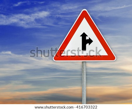 Triangle road sign the right direction on rod with cloudy sky - stock photo