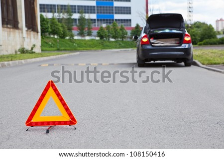 Triangle warning sign on road foreground and broken car with blinker lights on road wayside - stock photo