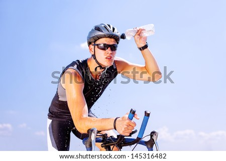 Triathlete cools his head while cycling on a bicycle - stock photo