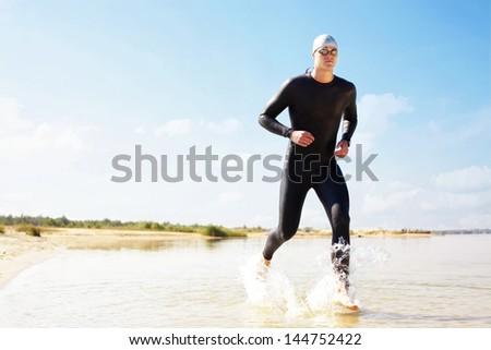 Triathlete running in to the water on triathlon race. - stock photo