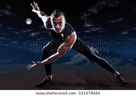 Triathlon runner man outdoor in night desert landscape. Extreme fitness sport. Standing in stretch position. - stock photo