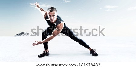 Triathlon runner man outdoor in winter snow landscape. Extreme fitness sport. Standing in stretch position. Warming up.