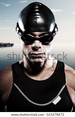 Triathlon swimmer man with cap and glasses outdoor at a lake with blue cloudy sky. Extreme fitness sport. Close-up portrait.