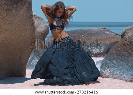 Tribal style girl on the beach - stock photo