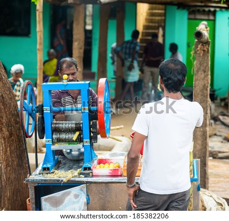 TRICHY, INDIA - FEBRUARY 15: An unidentified man squeezes the juice from the cane on a dedicated machine (juicer). India, Tamil Nadu, near Trichy. February 15, 2013 - stock photo