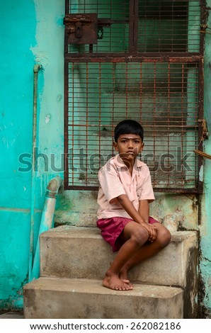 TRICHY,  INDIA - FEBRUARY 15: Unidentified Indian boy sitting near colorful wall of his house at street on February 15, 2012. India, Trichy, Tamil Nadu - stock photo