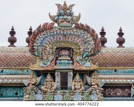 Trichy, India - October 15, 2013: Closeup of bow decoration on the Vimanam of one Gopuram at Shirangam temple. Monster face on top of pastel-colored bow with humans, elephants, horses, parrots, dogs - stock photo