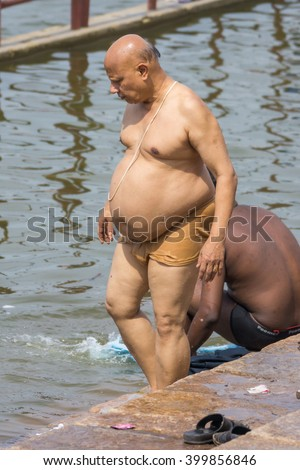 Trichy, India - October 15, 2013: One obese man descends into the Cauvery River for his ritual bath. He is naked except for brown underpants. Seen at Amma Mandapam. - stock photo
