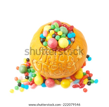 Trick or treat Halloween pumpkin filled with multiple coloful candies and sweets, composition isolated over the white background - stock photo