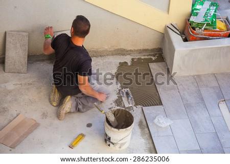 TRIESTE, ITALY - APRIL, 22: Worker Installing ceramic floor tiles on April 22, 2015 - stock photo