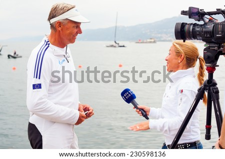 TRIESTE, ITALY - OCTOBER, 12: The journalist of the Slovenian tv, RTV interviewing Jochen Schuman skipper of the Esimit Europa 2, sailboat winner of  the 46 th Barcolana on October 12, 2014 - stock photo