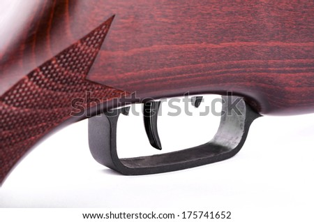 Trigger a hunting rifle on a white background closeup - stock photo