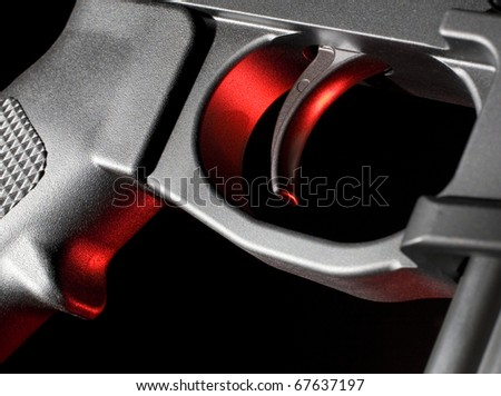 Trigger on an assault rifle that has red gels from the side - stock photo