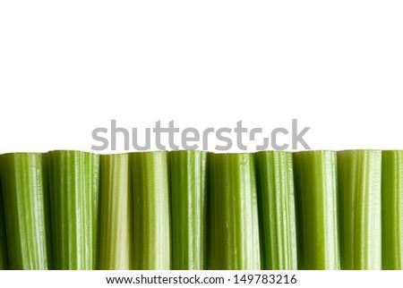 Trimmed green celery stalks against white - stock photo