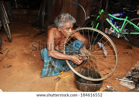 TRINCOMALEE, SRI LANKA - JANUARY 07: Unknown bicycle repairman working in his front yard on January 07.2014,Trincomalee,Sri Lanka.People in Sri Lanka suffer of poverty and try to get some money in this way - stock photo