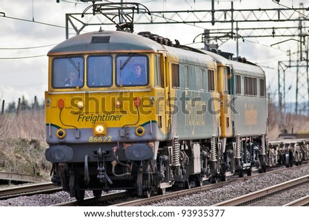 TRING, ENGLAND - JANUARY 19: Two class 86 electric locos pass northbound with an empty freight train on January 19, 2012 at Tring. These locos are nearly 50 years old and still on mainline service - stock photo
