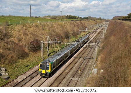 TRING, UK - APRIL 5: A class 350 London Midland EMU passenger train passes Tring cutting heading towards London Euston on April 5, 2016 in Tring. LM operate 77 class 350 units calling at 146 stations