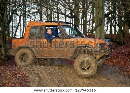 TRING, UK - NOVEMBER 25: An unnamed driver negotiates his vehicle through a muddy slope into a water filled bombhole at the Burnham OR club trial meeting on November 25, 2012 in Tring - stock photo