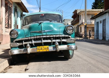 TRINIDAD, CUBA - FEBRUARY 5, 2011: Oldtimer car parked in Trinidad. Cuba has one of the lowest car-per-capita rates (38 per 1000 people in 2008). - stock photo