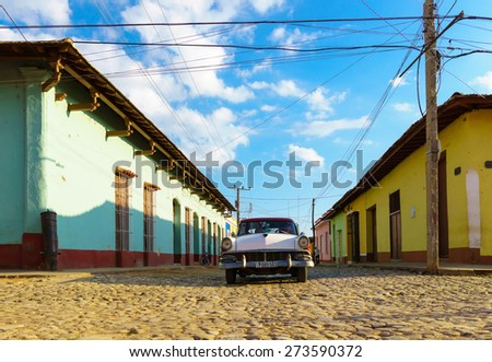Trinidad, CUBA - JANUARY 19, 2014:: Old classic American car and the colourful colonial building walls of Trinidad.Where old cars are relic of Cuban revolution and still attracts tourists. - stock photo