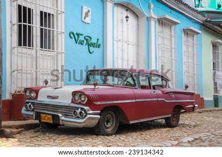 Trinidad, CUBA - JANUARY 28, 2013: Old classic American car park on street of Trinidad,CUBA. Old American cars are iconic sight of Cuba street. - stock photo