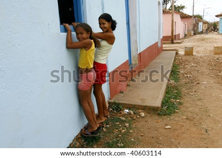 TRINIDAD, CUBA - MARCH 22: Two cute girls on March 22, 2009 in Trinidad, Cuba. Cuban children are expected/required to work to support their families, the problem they also face is child prostitution - stock photo