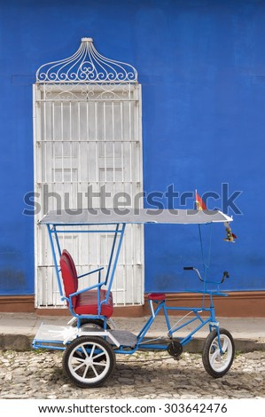 """Trinidad, Cuba - typical cuban rickshaw, or """"bicitaxi"""", in front of the entrance of a colonial house. - stock photo"""