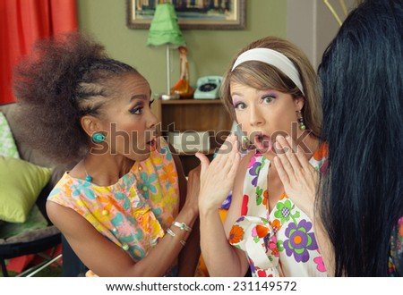 Trio of concerned ladies in 1960s dress talking - stock photo
