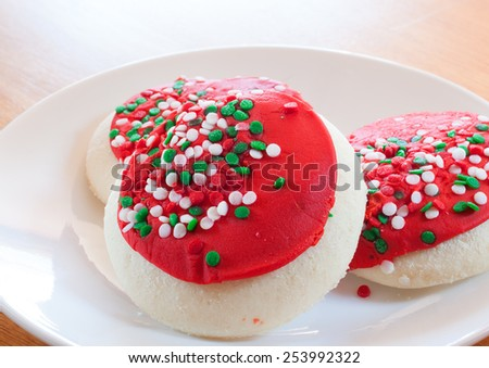 Trio of cookies decorated with red and sprinkles for Christmas - stock photo