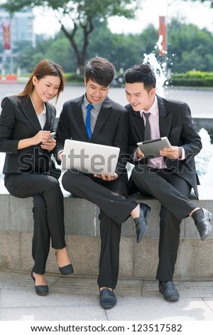 Trio of elegant business workers meeting outdoors on a sunny summer day - stock photo