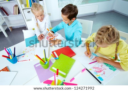 Trio of friends enjoying drawing in an after-school club - stock photo