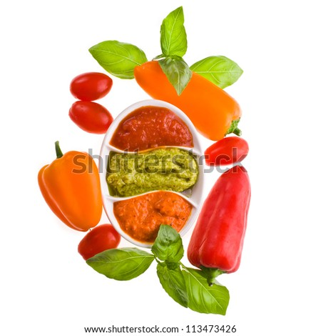 trio of sauces - pepper sauce, tomato, basil - dishes for sauces with three different kinds of sauces, a branch of basil and pepper and tomato  isolated on white background - stock photo