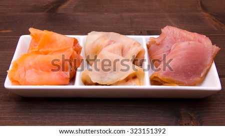 Trio of smoked fish on platter over wooden table
