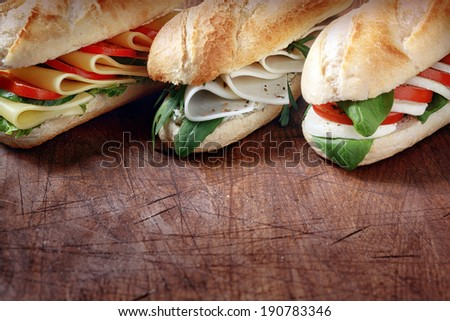 Trio of tasty vegetarian baguettes with assorted cheese fillings with basil, rocket, tomato and lettuce on crusty freshly baked rolls, rustic wooden tabletop with copyspace - stock photo