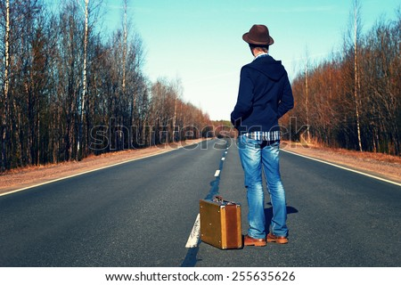 Trip to holiday. Travel to a week-end.The man in jeans with a suitcase. - stock photo