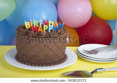 Triple Chocolate Cake frosted embossed with diamond impression on the sides hand crafted Chocolate frosting roses on top Isolated on yellow table balloons in background happy birthday candles  - stock photo